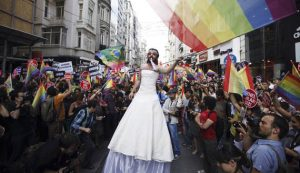 A participant wears a bridal dress as he waves the rainbow flag during a gay pride parade in central Istanbul
